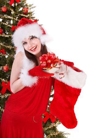 Girl in santa hat holding christmas socks and gift box near christmas tree.  Isolated.