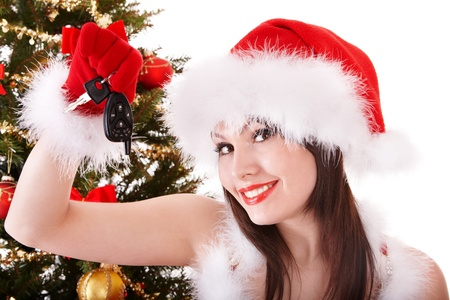 Christmas girl in santa hat holding auto keys. Isolated. Stock Photo