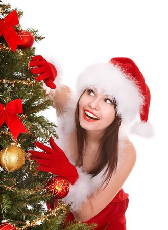 Girl in santa hat by christmas tree.  Isolated. photo