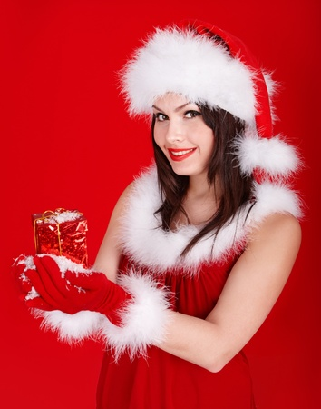 snow maiden: Young woman in Santa hat holding gift box on red background. Stock Photo