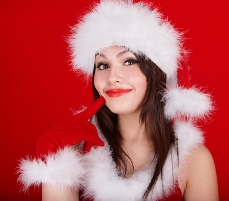 Christmas girl in red santa hat. Red background. photo