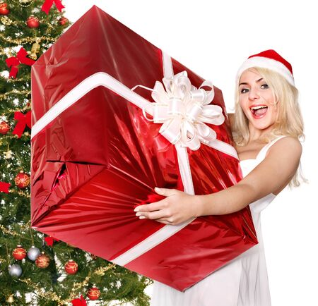 Girl in santa hat holding stack  gift box by christmas tree.. Isolated. Stock Photo - 11210038