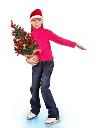 Happy young girl figure skating in Santa hat with Christmas tree. Isolated. photo