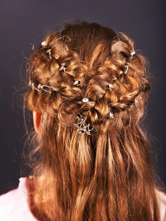 hair part: Rear view of  hairstyle with braiding. Black background.