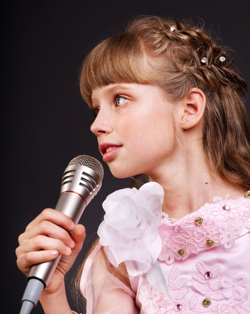 using voice: Singing of little girl in microphone.