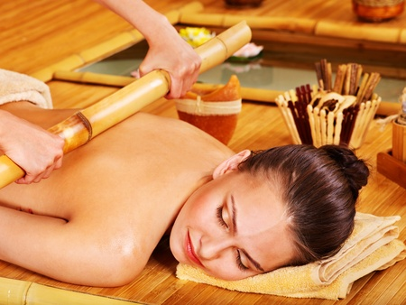 Young woman getting bamboo massage. Stock Photo