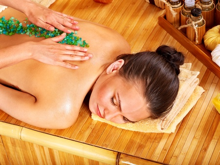 Young woman getting salt massage. photo