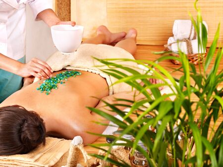 body conscious: Young woman getting salt massage.