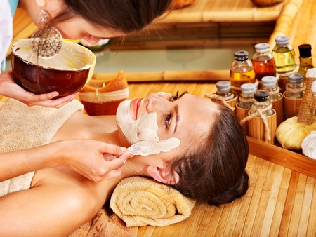 parlour: Beautiful girl having clay facial mask apply by beautician. Stock Photo