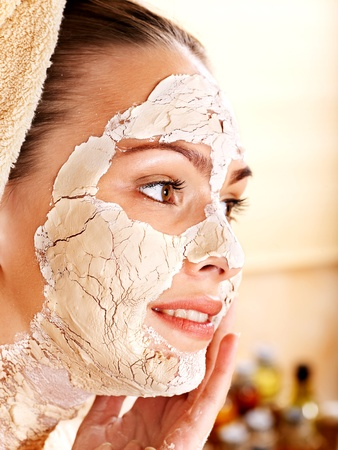 Beautiful girl having clay facial mask. photo