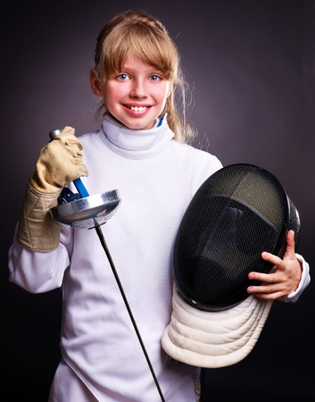 Child in fencing costume holding epee . Black background. photo