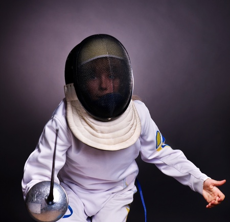 fencing: Child epee fencing lunge. Dark background.