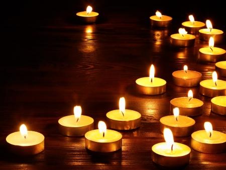 Grupo de velas encendidas sobre fondo negro. Foto de archivo