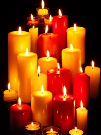 lit candle: Group of burning candles on  black background.