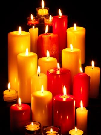 luz de velas: Grupo de velas encendidas sobre fondo negro.