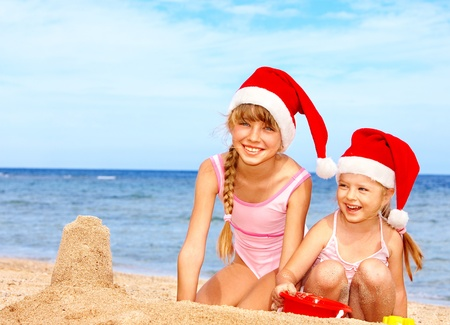 Children in santa hat playing on  beach. Summer New Year. photo