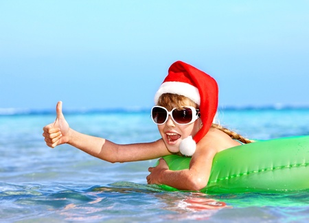 Child in santa hat  floating on inflatable ring in sea. Thumb up. Stock Photo
