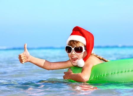 niños nadando: Niño en el sombrero de santa que flota en el anillo inflable en el mar. Pulgar hacia arriba. Foto de archivo