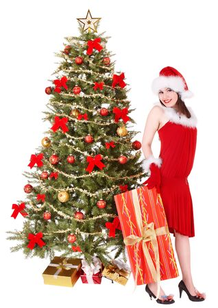Girl in santa hat holding  gift box by christmas tree.. Isolated. photo