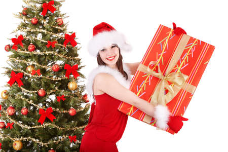 Girl in santa hat holding gift box near christmas tree.  Isolated. Stock Photo - 11439324