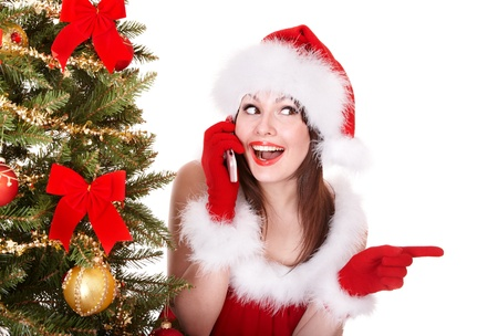 Girl in santa hat call mobile phone by christmas tree. Isolated. photo