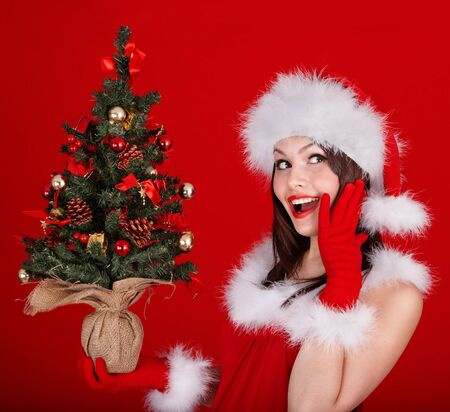 Girl in santa hat holding christmas tree. Red background. photo