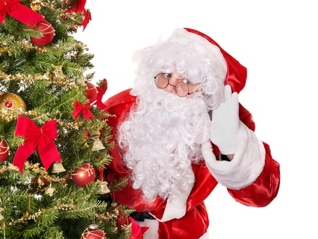 Santa claus with hand on ear by christmas tree.  Isolated. Stock Photo - 11439378