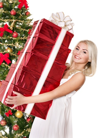 Girl in santa hat holding stack  gift box by christmas tree.. Isolated. photo