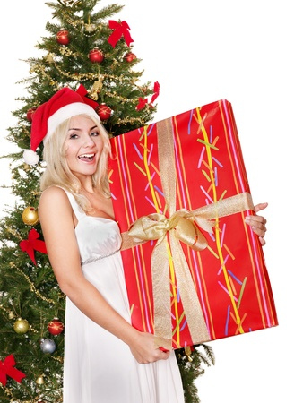 Girl in santa hat holding red gift box by christmas tree. Isolated. photo