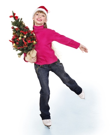 Happy young girl figure skating with christmas tree. Isolated. photo