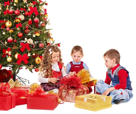 red christmas ball: Children with gift box near Christmas tree. Isolated. Stock Photo