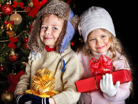 Children with gift box near Christmas tree. Outdoor. photo