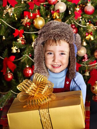 Child with gift box near Christmas tree. Outdoor. photo