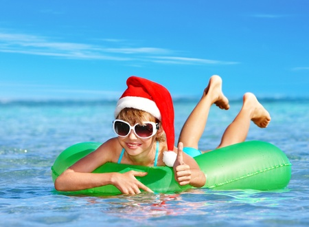 child swimsuit: Child in Santa hat  floating on inflatable ring in sea. Thumb up.
