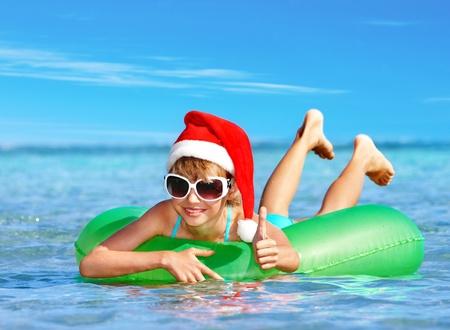Ni�o en Santa sombrero flotando en el anillo inflable en el mar. Pulgar hacia arriba. photo