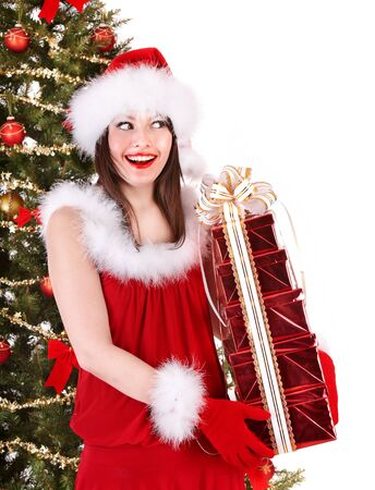 Girl in Santa hat with gift box near Christmas tree.  Isolated. photo