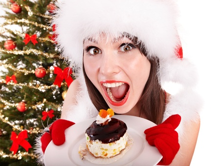 Girl in Santa hat eat cake on plate by Christmas tree. Isolated. photo