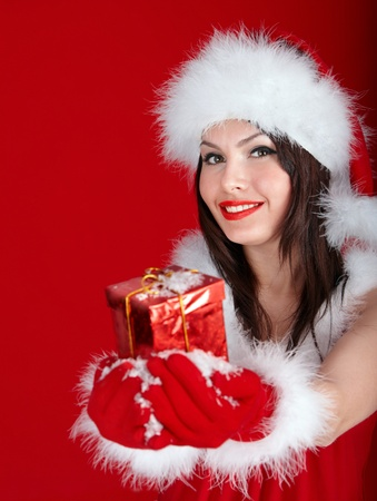 Young woman in Santa hat holding gift box on red background. photo