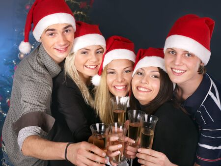 Group young people in Santa hat drink champagne at nightclub. photo
