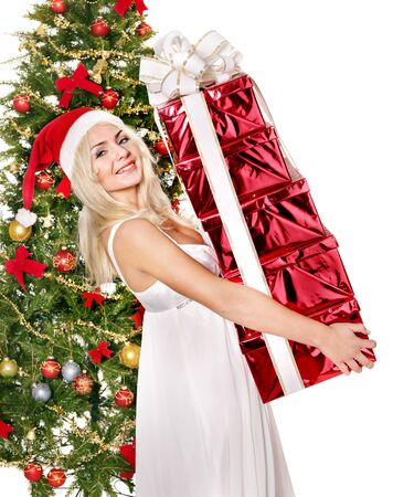 Girl in santa hat giving red gift box by christmas tree. Isolated. photo