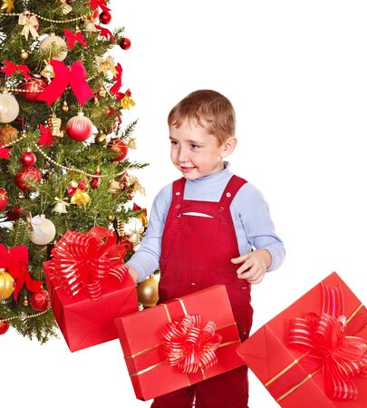 Child with gift box near Christmas tree. Isolated. photo