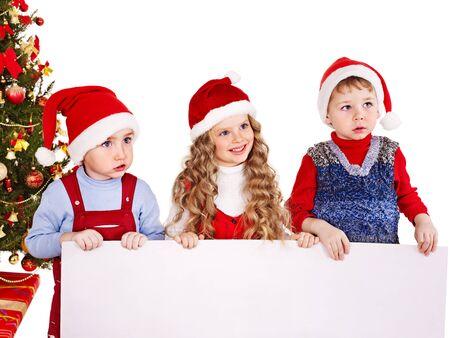 niños con pancarta: Los niños en Santa sombrero con la bandera cerca del árbol de Navidad. Aislados.