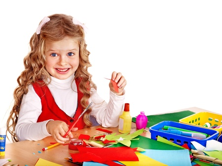 card making: Little girl with scissors and glue in school.
