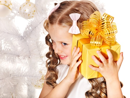 Child with gift box near white Christmas tree. Isolated. Stock Photo - 11439440