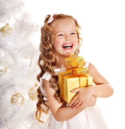christmas girl: Child with gift box near white Christmas tree. Isolated.