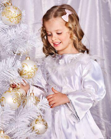 Child decorate white Christmas tree. Isolated. photo