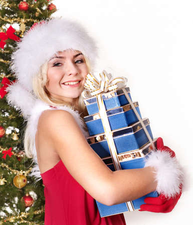 Girl in Santa hat holding stack  gift box by christmas tree. Isolated. photo