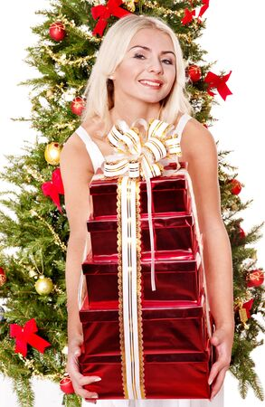 Girl  giving stack gift box near Christmas tree.  Isolated. photo
