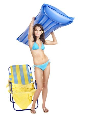 Girl in bikini on beach with mattress. photo
