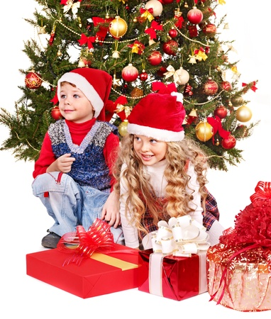 Children in Santa hat with gift box near Christmas tree. Isolated. photo